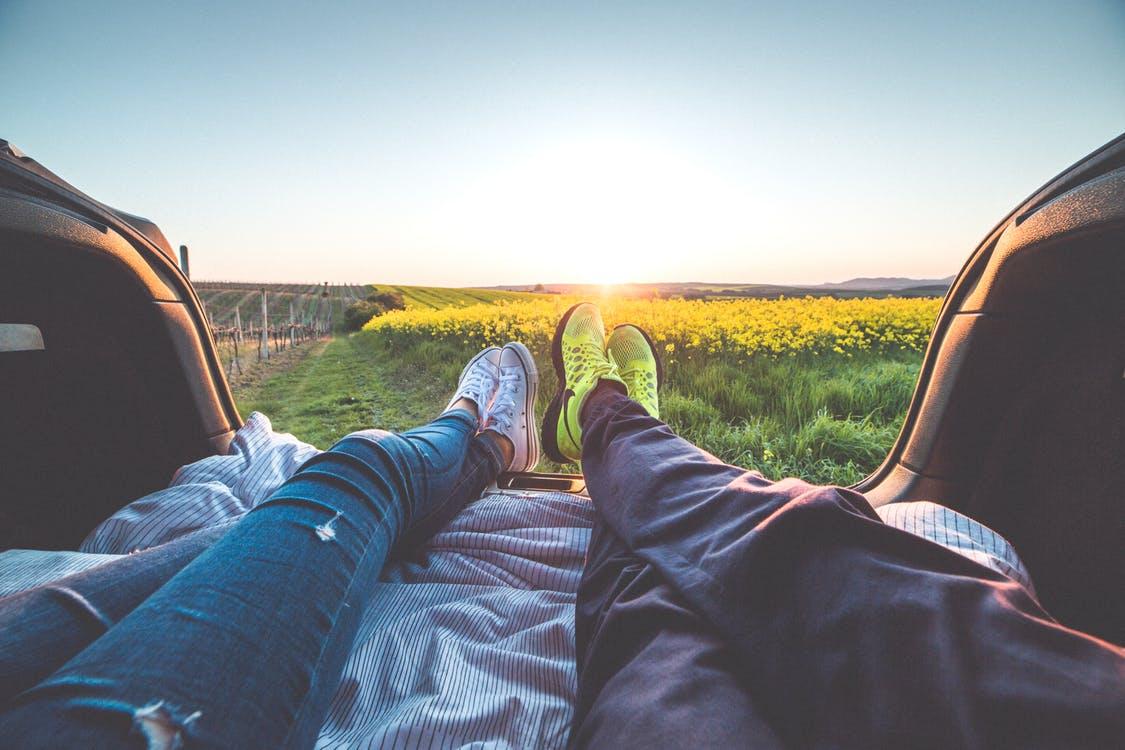 jeune couple regardant un paysage dans leur voiture